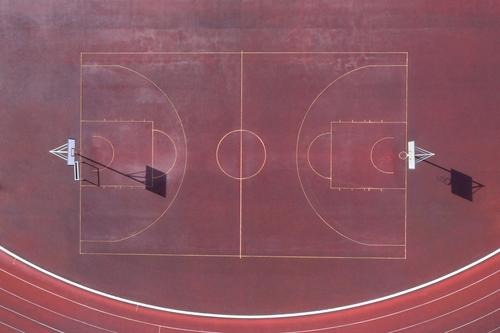 ein einfacher Basketballplatz von oben Basketballfeld Linien Sport-Linien Basketball-Linien Sportplatz Asche rot kleiner Basketballplatz Sonne Schatten Ball