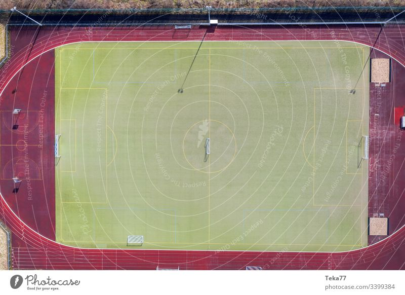 ein Fußballfeld von oben Fußballfeldtor Fußballtor Linien Sport Sportplatz grün kleiner Fußballplatz Gras Sonne Schatten Laufbahn rennen Aschefeld