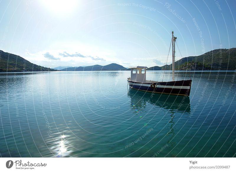 Dunkelblaues Fischerboot in einer Bucht verankert ägäisch Boot Windstille Wolken dunkelblau Insel Hügel mediterraner Meer alt friedlich Reflexion & Spiegelung