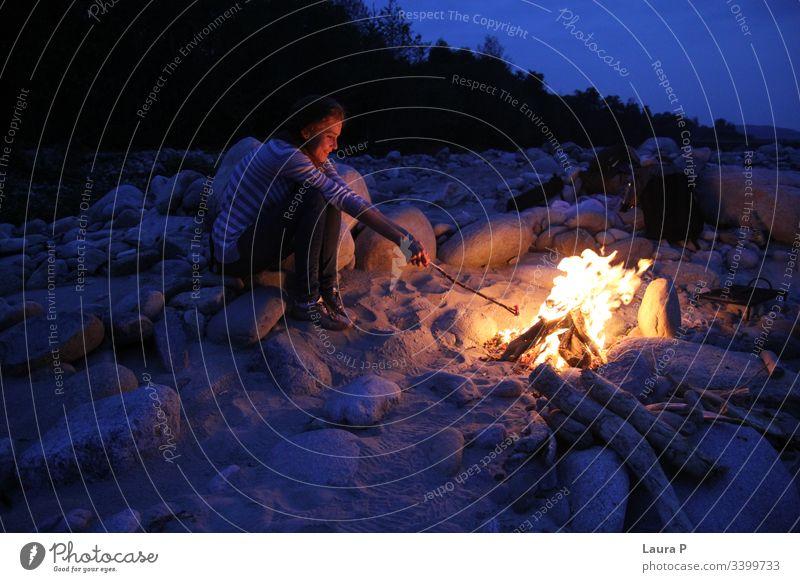 Frau hält abends einen Stock neben einem Lagerfeuer Junge Frau kleben außerhalb im Freien Lagerfeuerstimmung Feuer Farbfoto Außenaufnahme heiß Nacht Feuerstelle