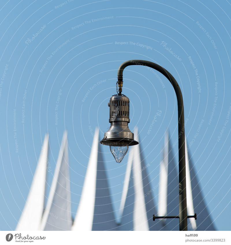 Ansicht einer Strassenlampe gegen tiefblauen Himmel und weißer Krone minimalistisch Lampe Straßenbeleuchtung Laterne Leuchte Fahne Fähnchen Blauer Himmel