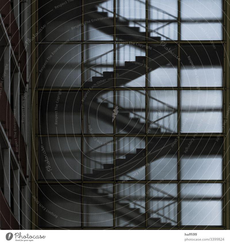 Aussenansicht eines Treppenhauses mit matter Fassade aus Glas Schwache Tiefenschärfe Kontrast Licht Schatten Hochhaus Milchglas transparenz diffus dunkel düster