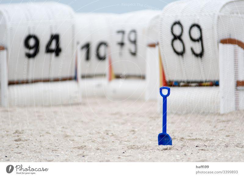 blaue Schaufel im Fokus vor unscharfen weißen Strandkörben am Strand Strandkorb Kinderschaufel Urlaub Erholung Küste Meer Sand Ostseestrand