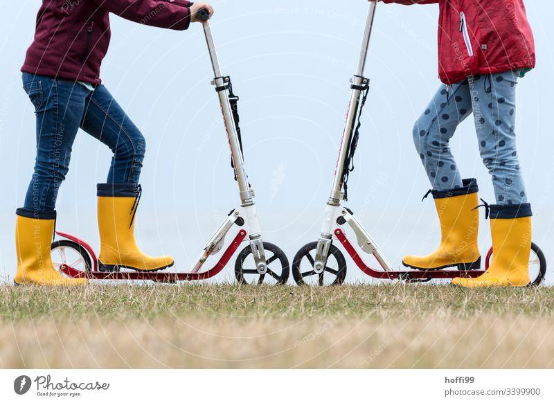 Roller Rad an Rad mit gelben Gummistiefeln Tretroller Spielen Kinder Spielzeug Spielplatz Duell