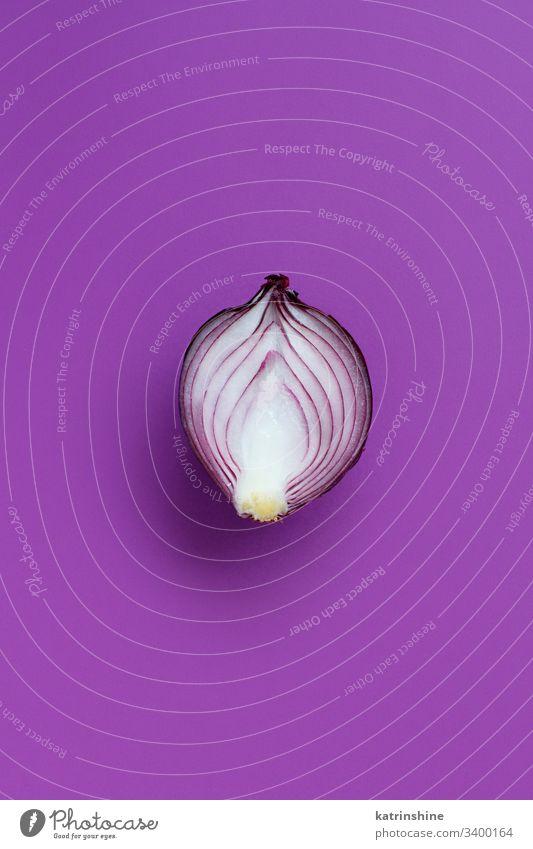 Violette Zwiebel auf violettem Hintergrund purpur Draufsicht oben rot aufgeschnitten Hälfte Lebensmittel Gesundheit roh organisch Gemüse Bestandteil Vegetarier