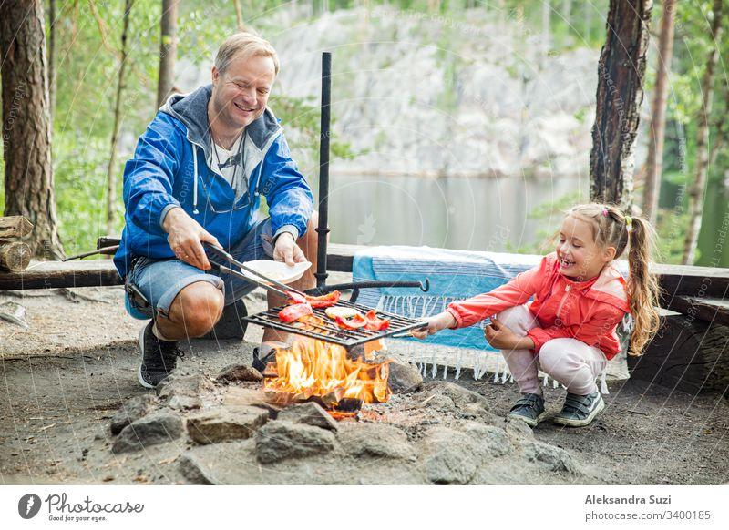 Mann und seine kleine Tochter grillen im Wald am felsigen Seeufer, machen ein Feuer, grillen Brot, Gemüse und Marshmallow. Familie erkundet Finnland. Skandinavische Sommerlandschaft.