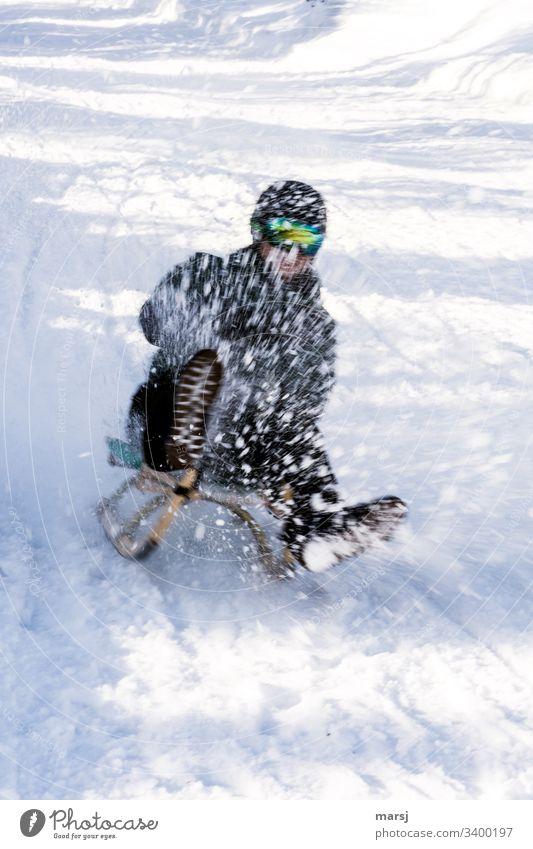 Nicht erkennbarer Mensch hat im wild spritzenden Schnee viel Spass beim Rodeln spaß-faktor Spaß schnee Winter Außenaufnahme kalt Freizeit & Hobby Sport
