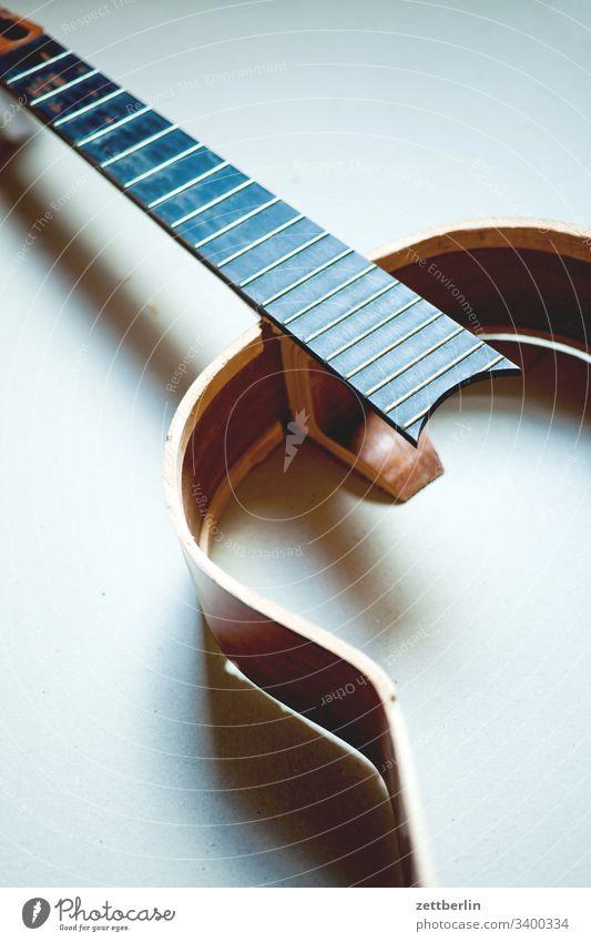 Gitarrenwrack bruch bruchstelle decke gitarre hals innen instrument kaputt menschenleer musikinstrument saiteninstrument schaden teile textfreiraum unfall