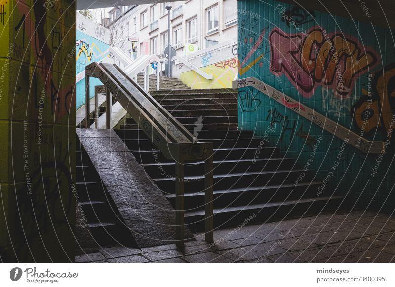 Treppe mit Graffiti Treppengeländer dunkel urban Stadtansichten Unterführung Darmstadt Großstadt Pfeil Farben taumeln dunkel und düster bunt gemischt