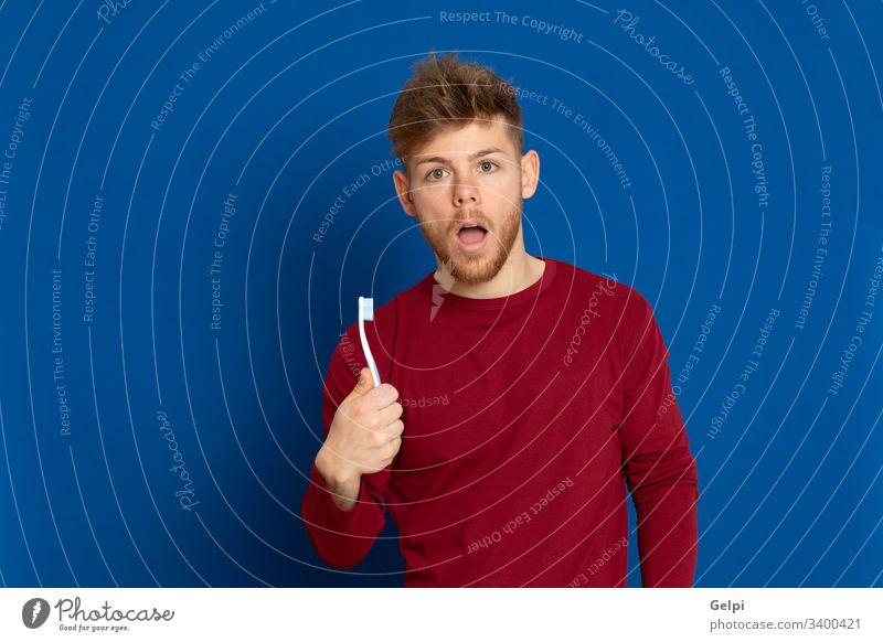 Attraktiver junger Mann mit rotem T-Shirt Typ blau Zahnersatz Zähne Zahnbürste Zahnarzt Hygiene Gesundheit überrascht Glück Erwachsener zwanzig männlich Model