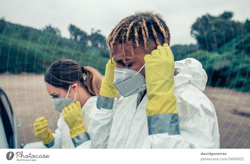 Jugendliche, die Schutzmasken aufsetzen Anlegen von Schutzmasken covid-19 Seuche Pandemie Virus Coronavirus bakteriologischer Schutzanzug Krankheit Gesundheit