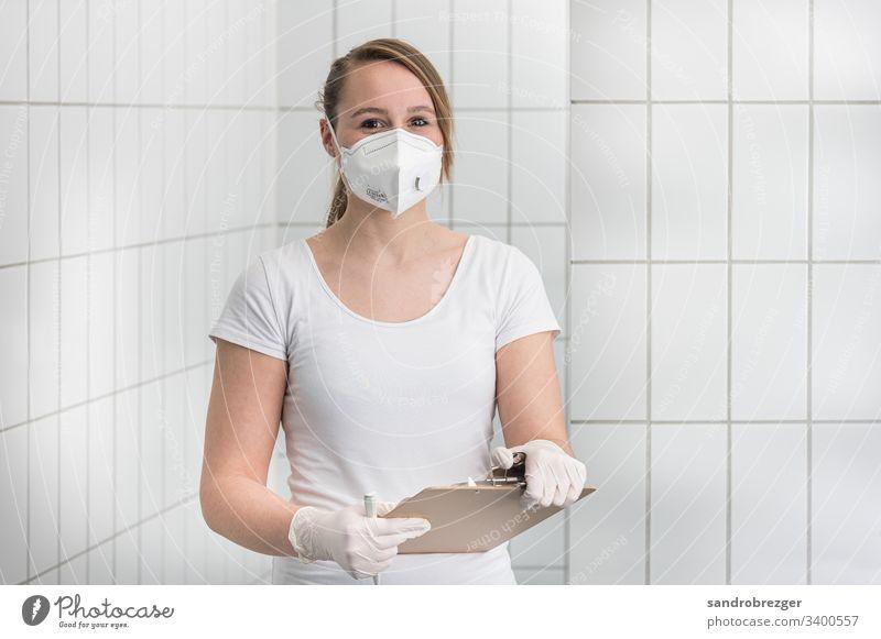 Arzthelferin mit Mundschutzmaske und Einmalhandschuhen Coronavirus COVID-19 Virus Krankheit Pandemie Epidemie Maske Schützen Handschutz Steril Medizin