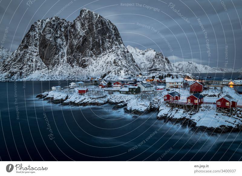 Hamnoy auf den Lofoten mit Aussicht auf die kleinen roten Häuschen die auf verschneiten Felsen stehen zur blauen Stunde Ferien & Urlaub & Reisen Ausflug Winter