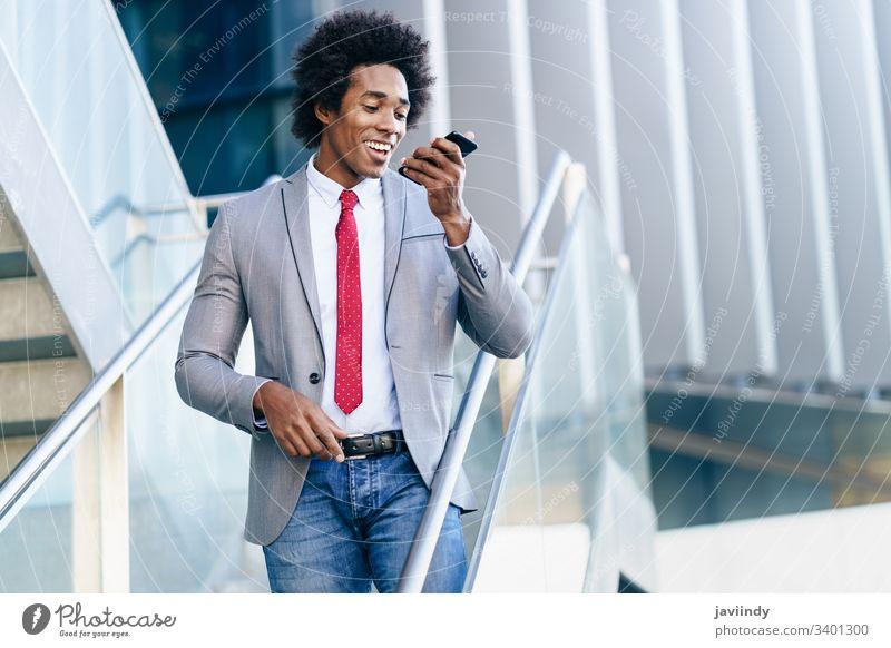 Schwarzer Geschäftsmann mit einem Smartphone in der Nähe eines Bürogebäudes schwarz lockig Afro-Look Business du Behaarung Anzug Afrikanisch männlich