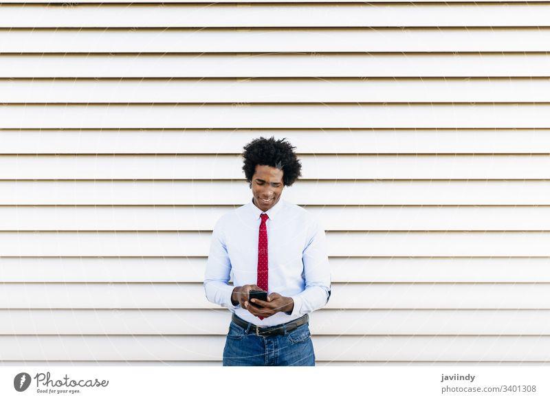 Schwarzer Geschäftsmann mit einem Smartphone mit weißem Jalousien-Hintergrund schwarz lockig Afro-Look Business du Behaarung Anzug Afrikanisch männlich