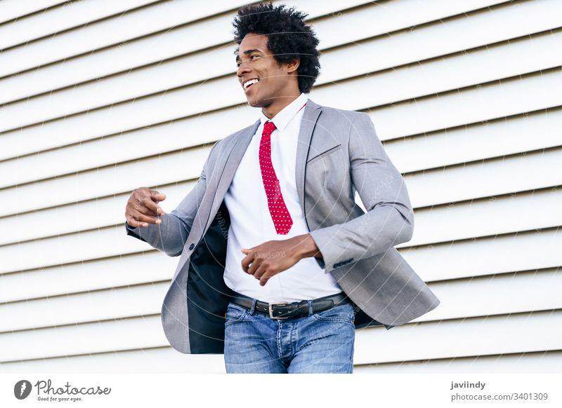 Fröhlicher schwarzer Geschäftsmann im Anzug, der im Freien tanzt. Glück lockig Afro-Look Freude du Behaarung Afrikanisch männlich Erwachsener Porträt Amerikaner