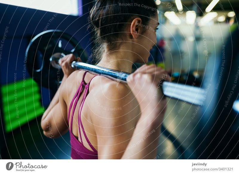 Athletische Frau im Fitnessstudio beim Heben von Gewichten im Fitnessstudio Gewichtheben Training passen Übung Sport Sportbekleidung Lifestyle jung sportlich