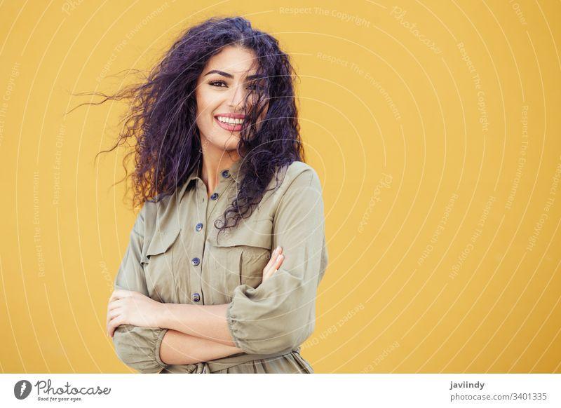 Junge arabische Frau mit lockigem Haar im Freien Behaarung Frisur Lächeln schön Mädchen Schönheit jung eine Mode copyspace nahöstlich gelb grün Model