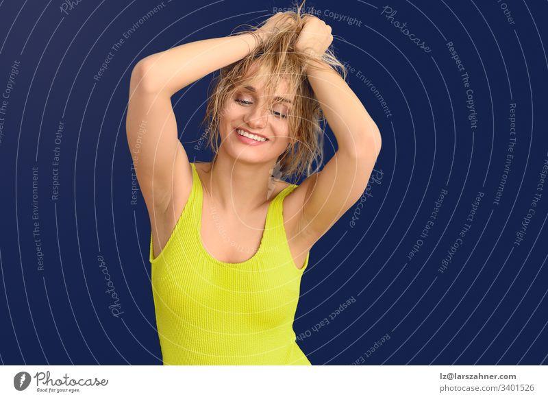 Glückliche, unbeschwerte blonde Frau mit Händen an den Haaren aktiv Jugendlicher Hintergrund blau Fotokamera sorgenfrei farbenfroh Kopie niedlich energetisch