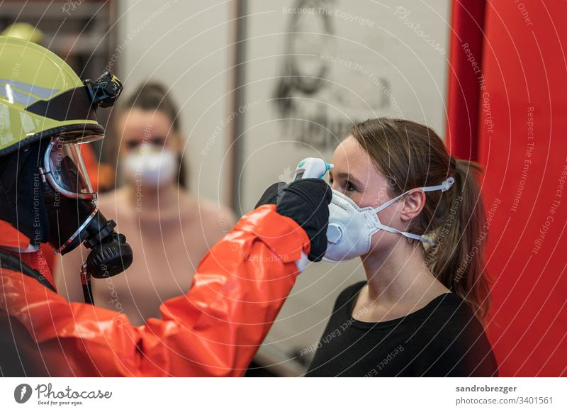 Bei Frauen mit Mundschutz wird Fieber gemessen Coronavirus COVID-19 Virus Krankheit Pandemie Epidemie Maske Schützen Einmalhandschuhe Handschutz Steril Medizin