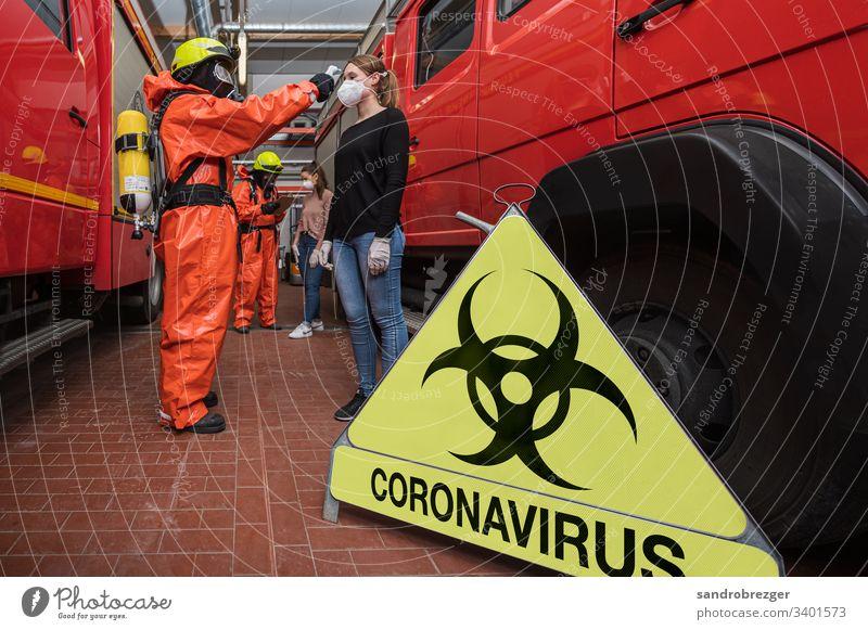Feuerwehrleute in Seuchenschutzanzügen untersuchen Personen mit Verdacht auf Corona Virus Coronavirus COVID-19 Krankheit Pandemie Epidemie Mundschutz Maske