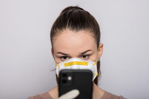 Frau mit Mundschutz und Einmalhandschuhen tippt auf dem Handy Coronavirus COVID-19 Virus Krankheit Pandemie Epidemie Maske Schützen Handschutz Steril Medizin