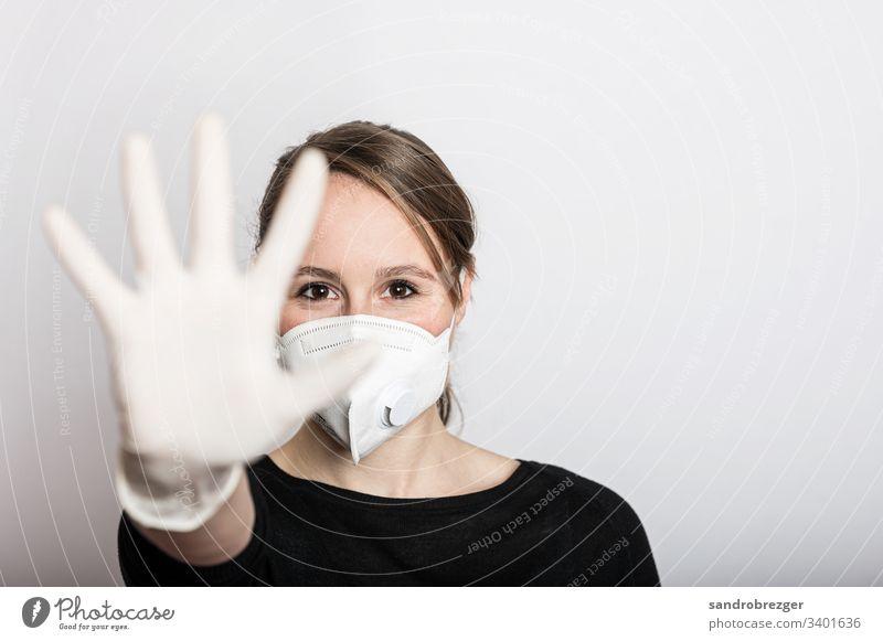 Frau mit Mundschutz und Handschuhen stoppt die Corona Virus Epidemie Coronavirus COVID-19 Krankheit Pandemie Maske Schützen Einmalhandschuhe Handschutz Steril