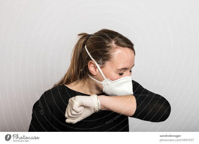 Frau mit Mundschutz und Einmalhandschuhen niest in die Armbeuge Coronavirus COVID-19 Virus Krankheit Pandemie Epidemie Maske Schützen Handschutz Steril Medizin