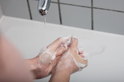 Frau beim Händewaschen Coronavirus COVID-19 Virus Krankheit Pandemie Epidemie Mundschutz Maske Schützen Einmalhandschuhe Handschutz Steril Medizin Quarantäne