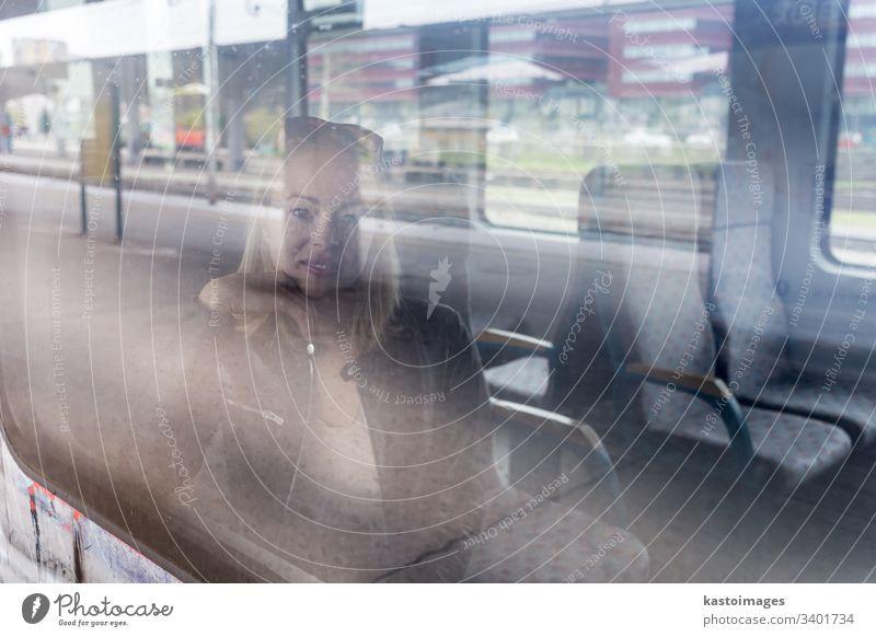 Junge Frau, die mit dem Zug reist und dabei aus dem Fenster schaut, während sie im Zug sitzt. Mädchen reisen jung Passagier Mitfahrgelegenheit Eisenbahn