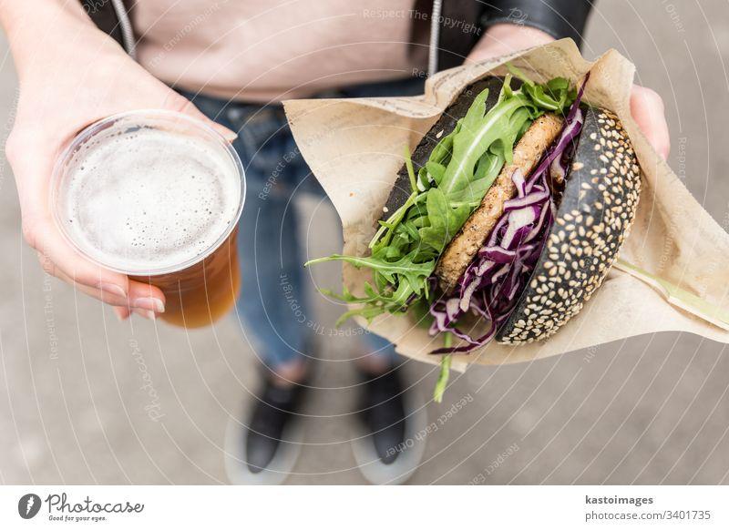 Frauenhände mit köstlichem vegetarischen Bio-Lachsburger und selbstgebrautem IPA-Bier. Burger Hände Salat Essen organisch Fleisch ungesund Grillrost Alkohol