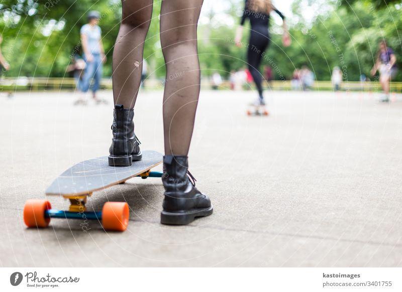Mädchen in schwarzen Stiefeln und Strümpfen beim Longboardfahren im Skateboard-Park. Aktives städtisches Leben. Städtische Subkultur. urban Holzplatte Sport