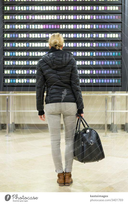 Weibliche Reisende, die eine Abflugtafel in der Flughafen-Terminalhalle kontrolliert. Anzeige Information Zeitplan reisen Ausflug Frau Fluggesellschaft Ankunft