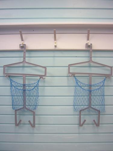 Drei leere Haken mit Garderobenbügel und Netz, an weißer Gaderobe, im geschlossenen Schwimmbad Schwimmen & Baden Schwimmsport Garderobenhaken garderobe
