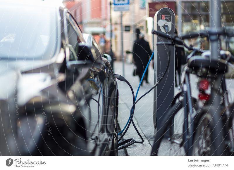 Das Aufladen moderner Elektroautos auf der Straße als Zukunft der Automobilindustrie. elektrisch PKW Fahrzeug Gebühr Verkehr Technik & Technologie Industrie