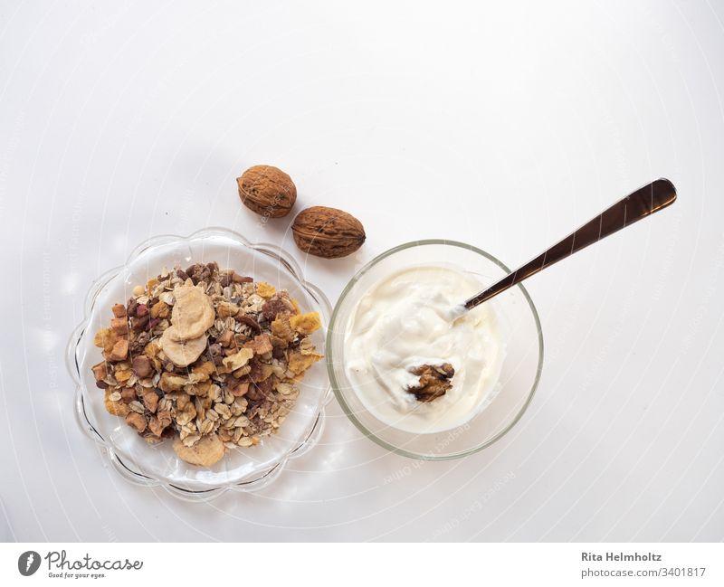 Frühstück mit Müsli und Joghurt Frühstücken lecker gesund frisch Glas Diat Snack Dessert weiß Gesundheit gesunde Ernährung Texfreiraum oben Wallnüsse Vitamine