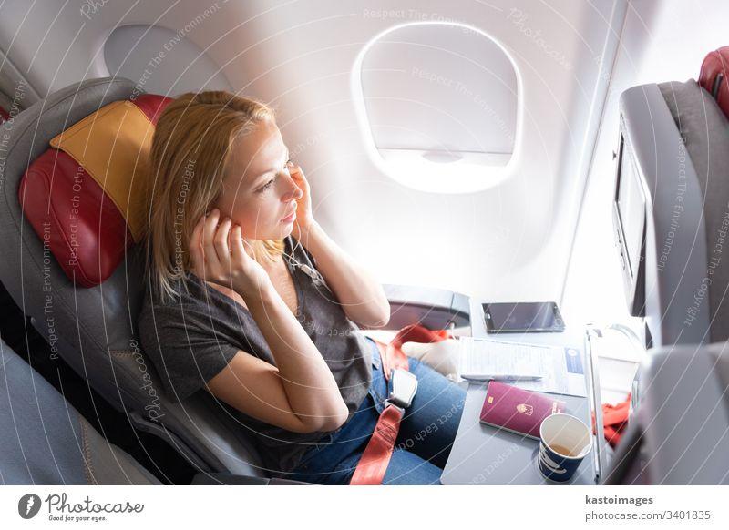 Frau, die in einem Passagierflugzeug fliegt und Musik hört. Flugzeug reisen jung Fluggerät Kabine Kaukasier Entertainment Kopfhörer Tasse Kaffee Smartphone