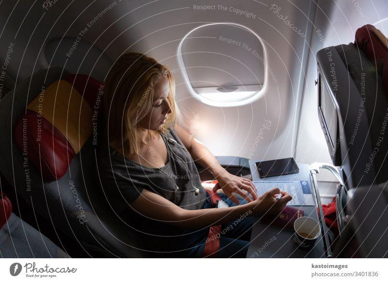 Gelegenheits-Frau, die in einem kommerziellen Passagierflugzeug fliegt und ein Einwanderungsformular ausfüllt. Flugzeug reisen Kabine Musik jung Fluggerät