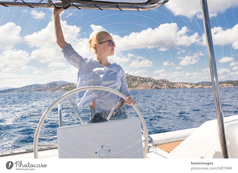Attraktive blonde Skipperin, die das schicke Katamaran-Segelboot an einem sonnigen Sommertag auf ruhigem blauen Meerwasser steuert. nautisch Lenkrad Boot Frau