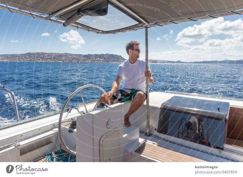 Attraktiver männlicher Skipper, der das schicke Katamaran-Segelboot an einem sonnigen Sommertag auf ruhigem blauen Meerwasser steuert. nautisch Lenkrad Boot