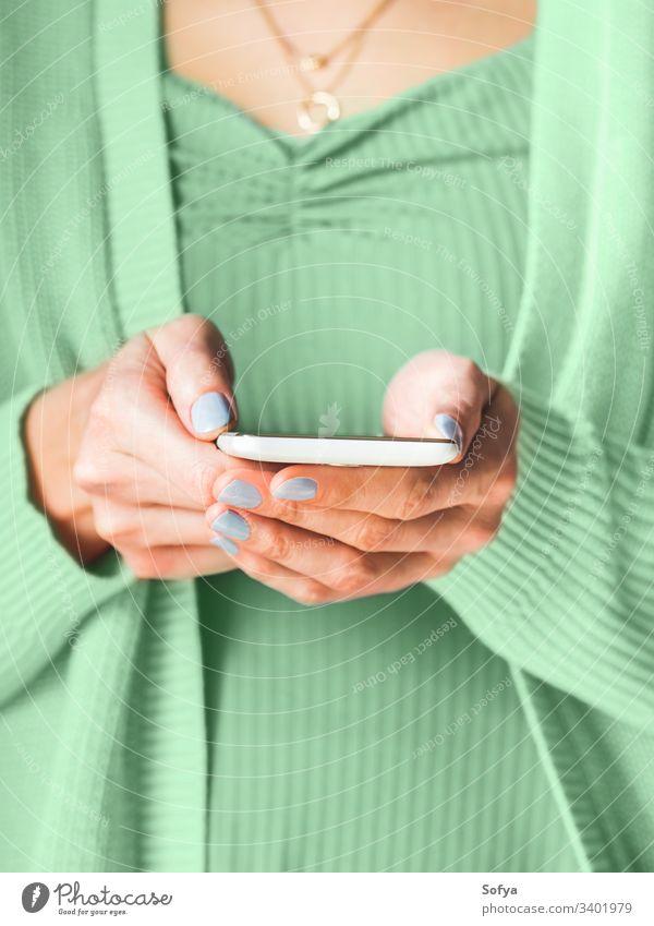 Frau mit weißem Smartphone. Mintgrüne Farbe von 2020 benutzend grüne Minze neo Farbe Jahr Hände Bildschirm Mobile Telefon Gerät Internet Anschluss Mitteilung