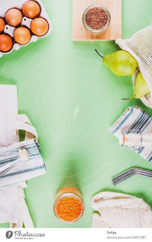 Abfallfreie Lebensmittel-Einkaufszubehör und -Werkzeuge - wiederverwendbare Stahlhalme, Baumwollnetzbeutel, Leinenservietten, Glasgefäße.  Flach auf minzgrünem Hintergrund liegend, Rahmendesign