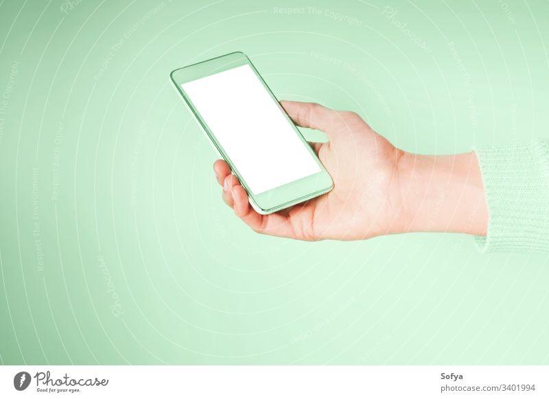 Hand mit Mobiltelefon und leerem weißen Bildschirm auf mintgrüner Farbe 2020 grüne Minze Mobile Telefon neo benutzend Farbe Jahr Hände Smartphone Frau Gerät