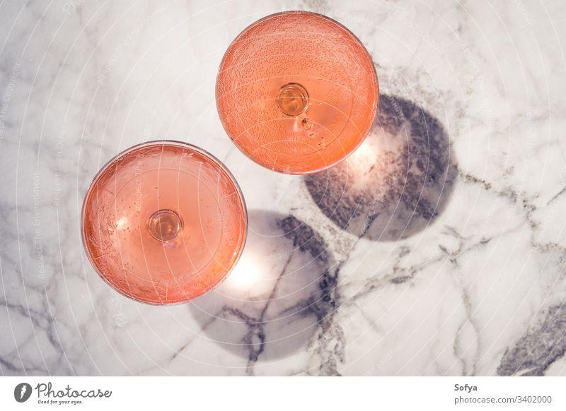 Zwei Kristallstielgläser mit Rosenwein im Freien auf Marmortisch in hartem Licht, das Schatten erzeugt Wein Roséwein weiß Glas Murmel Party rosa trinken