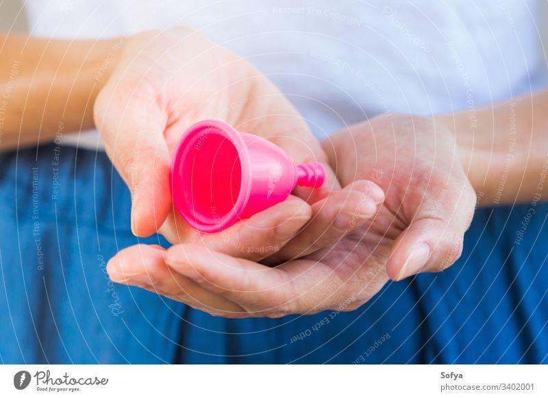 Frau hält eine rosa Menstruationstasse in den Händen. Nahaufnahme Tasse menstruell keine Verschwendung Produkt Aussehen Beteiligung Hygiene wiederverwendbar