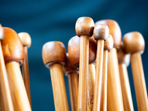 Holzstricknadeln Holzköpfe Gruppensymbol Stricken Detailaufnahme Nahaufnahme geringe Tiefenschärfe warme Farben Brauntöne Dunkelblau Textfreiraum oben
