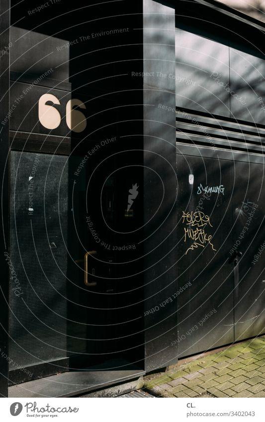 66 Tür Eingang Wand Menschenleer Haus Farbfoto Zahl Nummer Hausnummer Türgriff gehweg Graffiti authentisch dunkel dreckig Schmiererei Gebäude alt Außenaufnahme