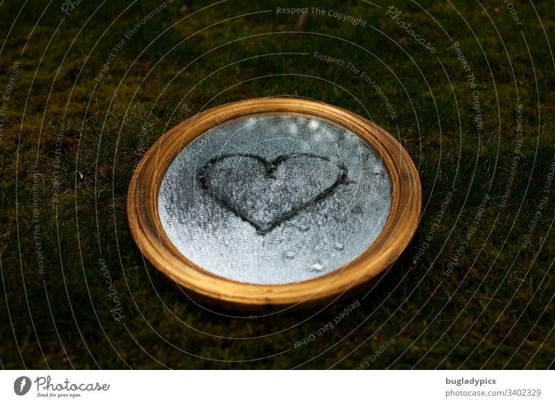 Goldener Spiegel liegt auf einer Wiese. Auf dem Spiegel befinden sich Wassertropfen. Ein Herz ist auf die Spiegelfläche gemalt. golden Moos Natur