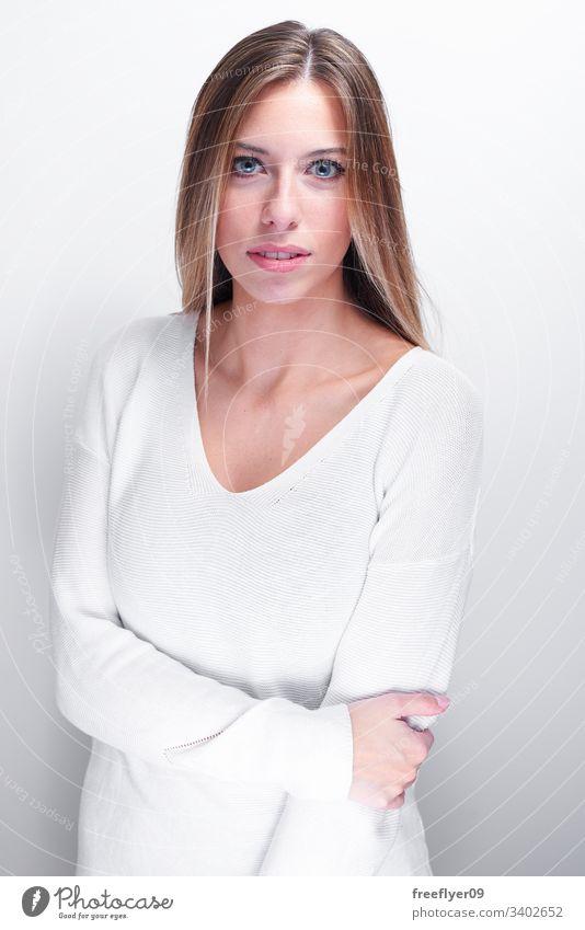 Schüchterne Frau, die die Kamera auf weißem Hintergrund betrachtet. langhaarig blond hoher Schlüssel blaue Augen klare Augen Porträt vertikal Glück Mädchen
