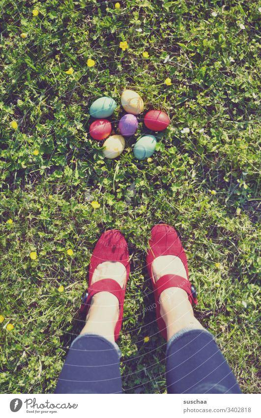 frau steht auf dem gras vor bunten ostereiern Frau stehen Beine Füße Damenschuhe rot Ostern Ostereier farbig gefärbt Schuhe bunte Eier gekochte Eier